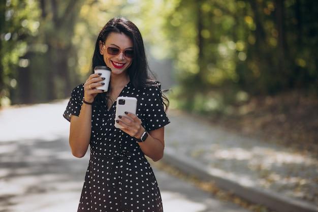 公園で電話で話している若い魅力的な女性 無料写真