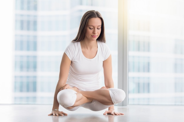 Young attractive woman in tolasana pose against floor window Free Photo