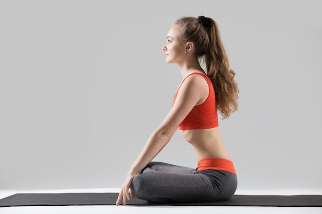 Young attractive woman in upward abdominal lock pose, grey studi Free Photo