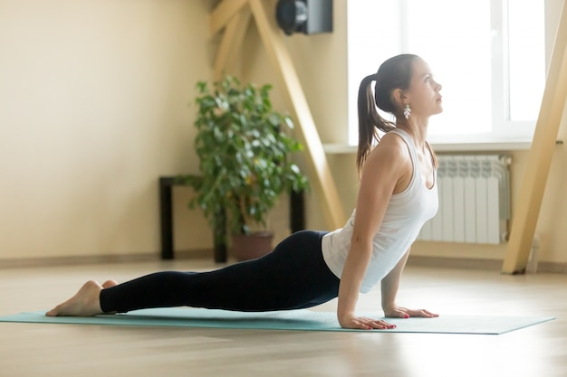 Young attractive woman in upward facing dog pose, home interior Free Photo