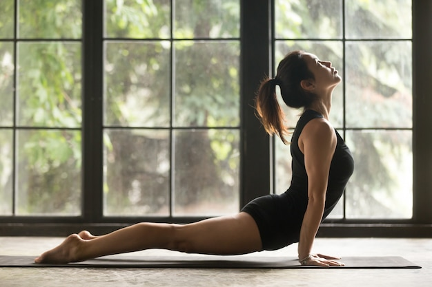 Young attractive woman in upward facing dog pose Free Photo