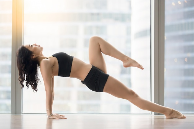 Young attractive woman in upward plank pose against floor window Free Photo