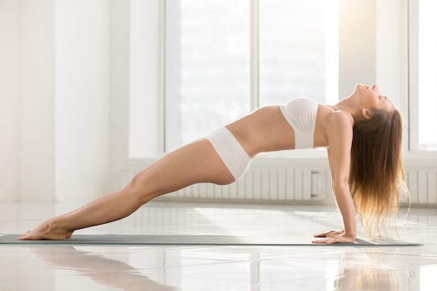 Young attractive woman in upward plank pose, white color backgro Free Photo