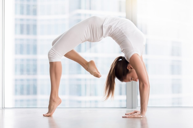 Young attractive woman in urdhva dhanurasana pose against floor window Free Photo