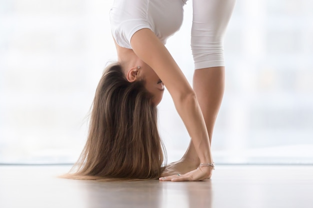 Young attractive woman in uttanasana pose Free Photo