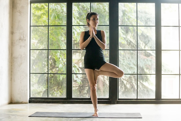 Young attractive woman in vrksasana pose, studio background Free Photo