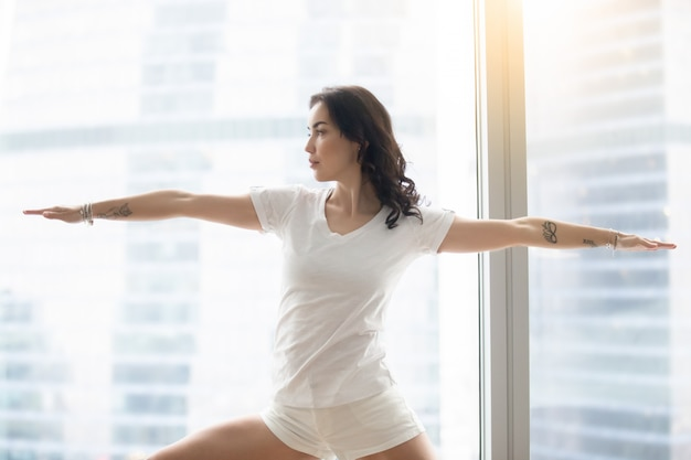 Young attractive woman in warrior two pose, against the window Free Photo