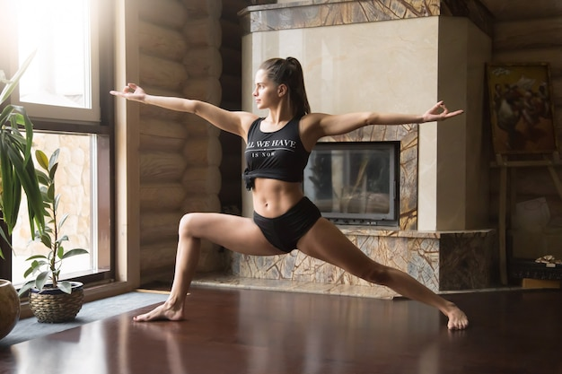 Young attractive woman in warrior two pose, home interior backgr Free Photo