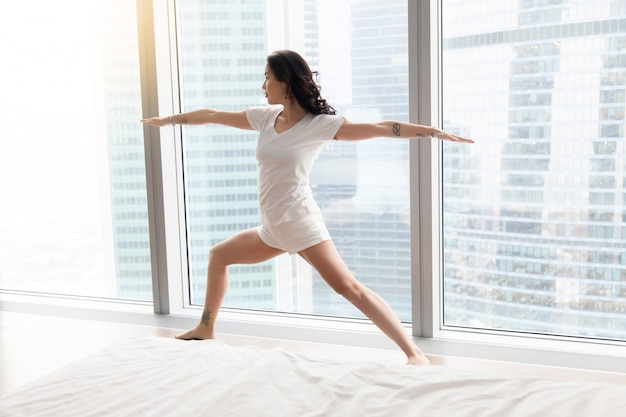 Young attractive woman in warrior two pose, white floor window Free Photo