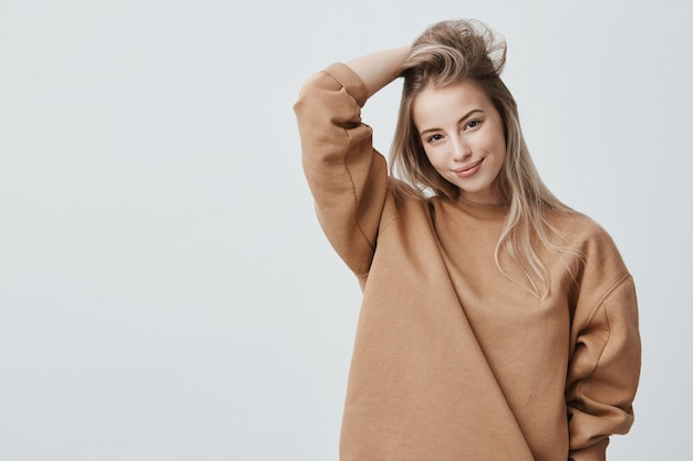 Young attractive woman wearing stylish long-sleeved sweatshirt and posing Free Photo
