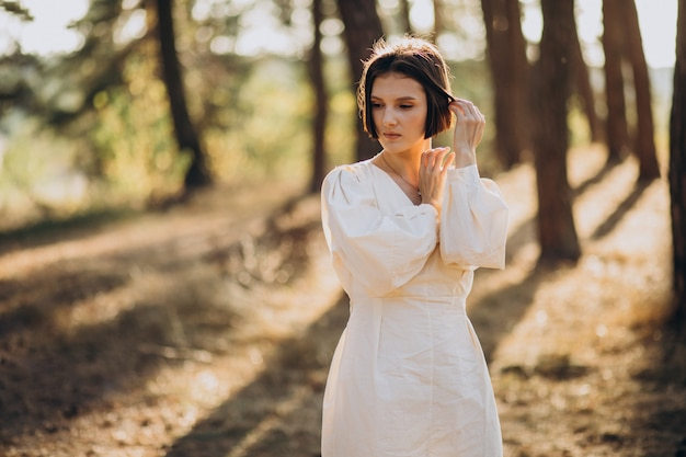Young attractive woman in white dress in forest Free Photo