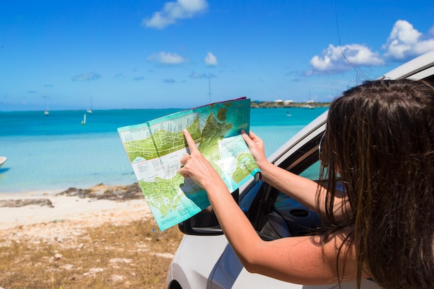 Young attractive woman with great map of island in the car Premium Photo