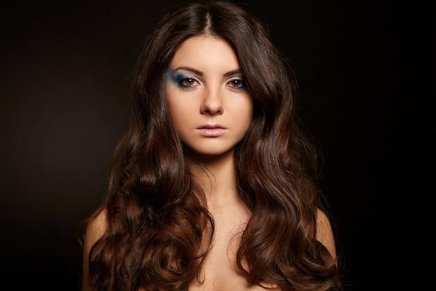 Молодая привлекательная женщина с длинными черными волосами яркий макияж, изолированных на черном фоне Бесплатные Фотографии