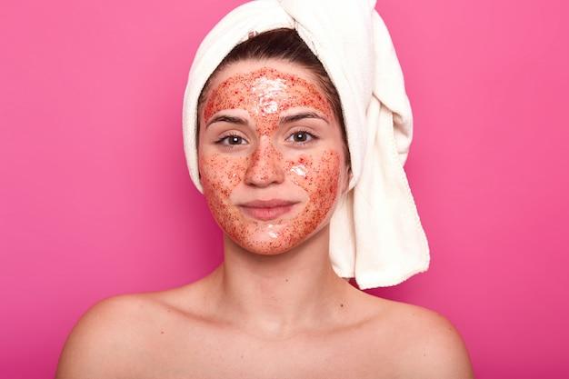Молодая привлекательная женщина с белым полотенцем на голове, имеет обнаженное тело, улыбаются изолированные над розовой стеной в студии, смотрит прямо в камеру, с красным скрабом на лице. Бесплатные Фотографии