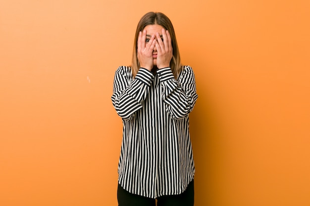 Young authentic charismatic real people woman against a wall blink through fingers frightened and nervous. Premium Photo