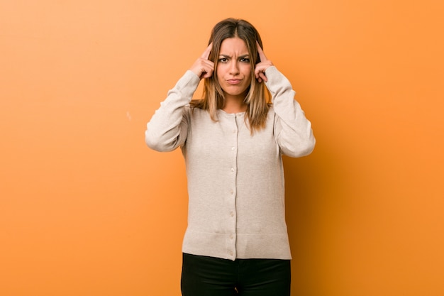 Young authentic charismatic real people woman against a wall focused on a task, keeping forefingers pointing head. Premium Photo