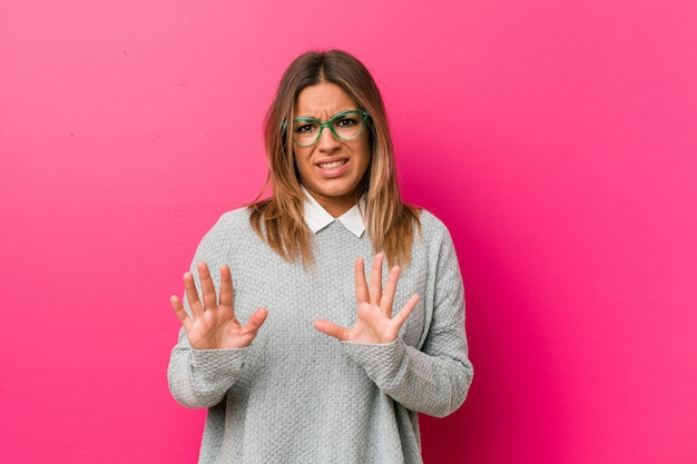Young authentic charismatic real people woman against a wall rejecting someone showing a gesture of disgust. Premium Photo