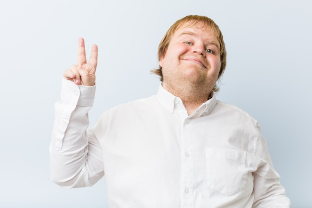 Young authentic redhead fat man joyful and carefree showing a peace symbol with fingers. Premium Photo