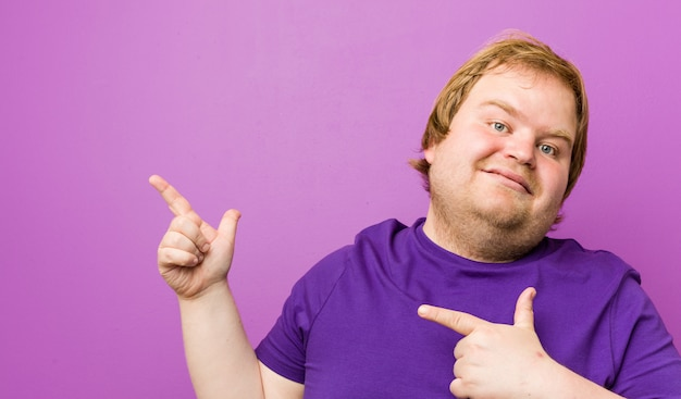 Young authentic redhead fat man pointing with forefingers to a , expressing excitement and desire. Premium Photo