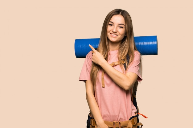 Young backpacker woman pointing to the side to present a product on isolated yellow wall Premium Photo