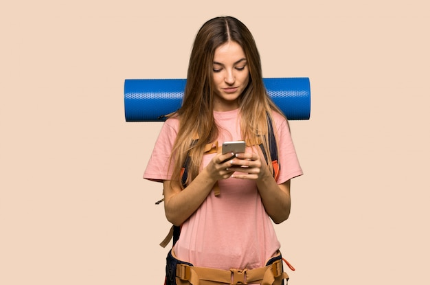 Young backpacker woman sending a message with the mobile on isolated yellow wall Premium Photo