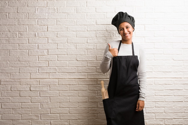 Young baker indian woman against a bricks wall cheerful and excited, smiling and raising her thumb up Premium Photo