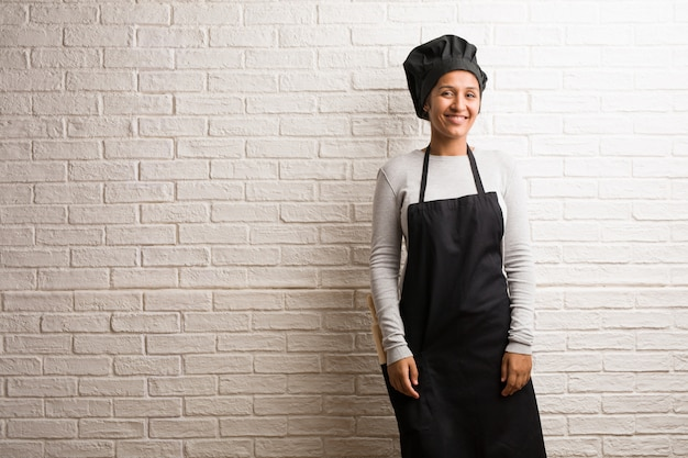Young baker indian woman against a bricks wall cheerful and with a big smile Premium Photo