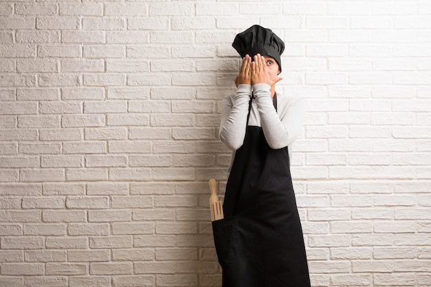 Young baker indian woman against a bricks wall feels worried and scared, looking and cover Premium Photo