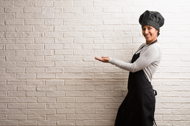 Young baker indian woman against a bricks wall holding something with hands Premium Photo