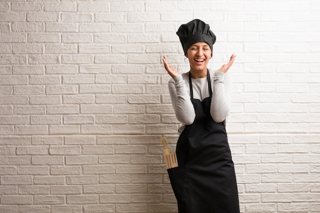 Young baker indian woman against a bricks wall laughing and having fun, being relaxed and Premium Photo
