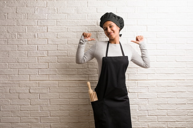 Young baker indian woman against a bricks wall proud and confident Premium Photo