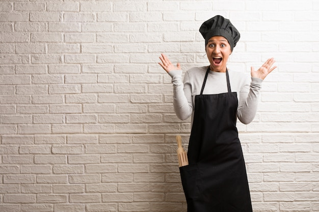 Young baker indian woman against a bricks wall screaming happy. Premium Photo