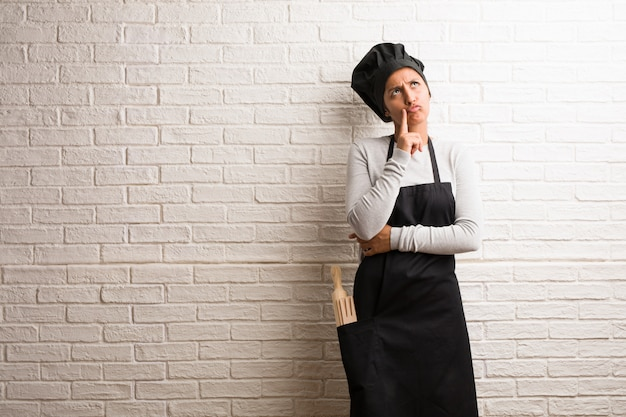 Young baker indian woman against a bricks wall thinking and looking up Premium Photo