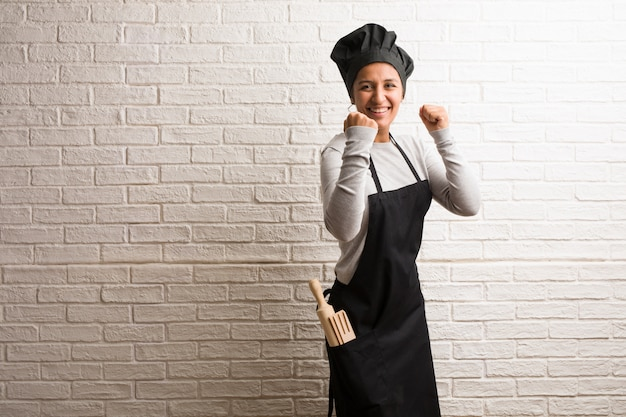 Young baker indian woman against a bricks wall very happy and excited Premium Photo