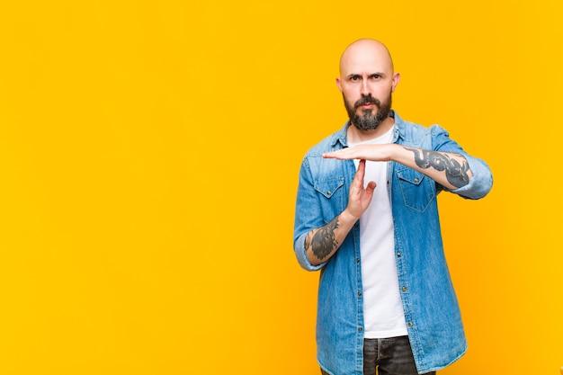 Молодой лысый и бородатый мужчина выглядит серьезным, строгим, злым и недовольным, делая знак тайм-аута Premium Фотографии