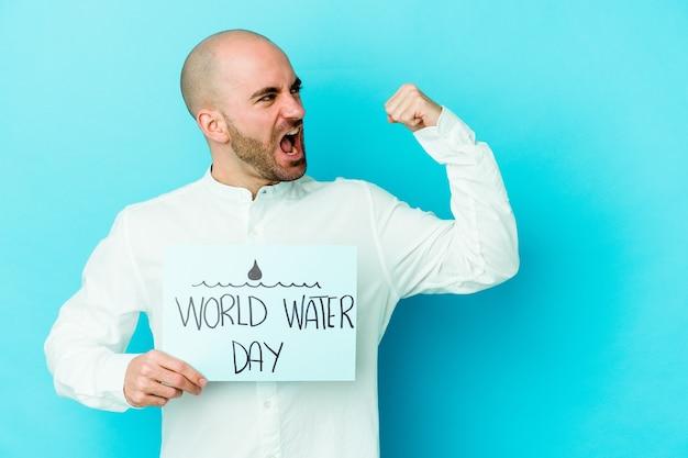 勝利、勝者の概念の後に拳を上げる青い壁に隔離された世界水の日を祝う若いハゲ男 Premium写真