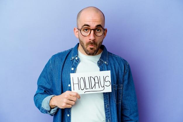 Молодой лысый мужчина, держащий праздничный плакат, изолированный на синей стене, пожимает плечами и в замешательстве открывает глаза Premium Фотографии