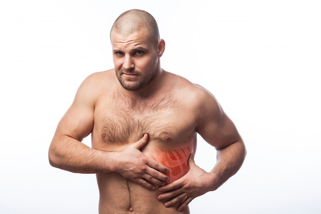 Young bald man sportive physique holds on sore rib Premium Photo