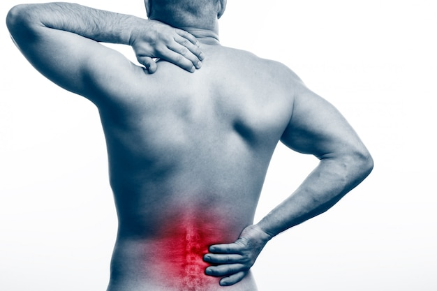 Young bald man sports physique holds a sick back Premium Photo
