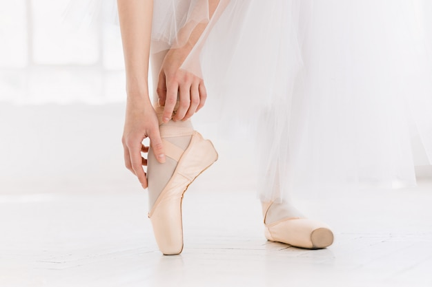 Young ballerina dancing, closeup on legs and shoes, standing in pointe position. Free Photo