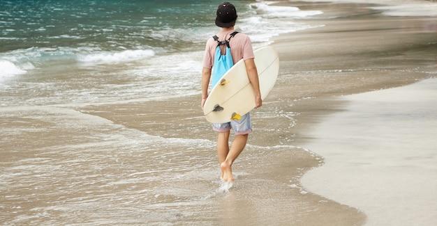 Молодой босоногий серфер с рюкзаком идет по пляжу, неся белый бодиборд под мышкой, возвращается домой после интенсивной езды Бесплатные Фотографии