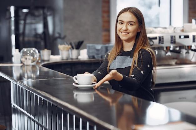 Молодая девушка бариста делает кофе и улыбается Бесплатные Фотографии