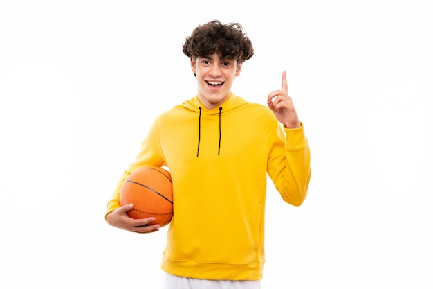 Young basketball player man over isolated white wall pointing up a great idea Premium Photo