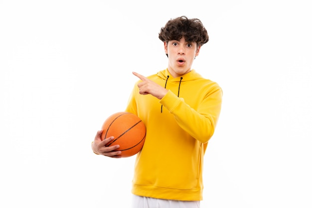 Young basketball player man over isolated white wall surprised and pointing side Premium Photo