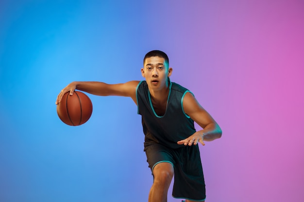 Young basketball player in motion on gradient studio background in neon light Free Photo