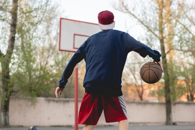 Young basketball player training to dribble outdoor on the asphalt court Premium Photo
