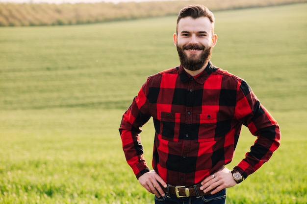 Young bearded agronomist standing in cultivated wheat crops field Premium Photo