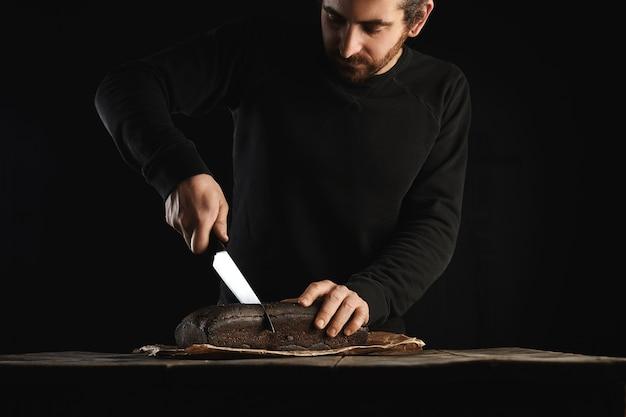 Uomo giovane panettiere barbuto in sudore nero utilizza un grosso coltello capo per affettare il pane di lusso fatto in casa da fichi e segale in carta artigianale sul tavolo in legno rustico isolato sul nero Foto Gratuite