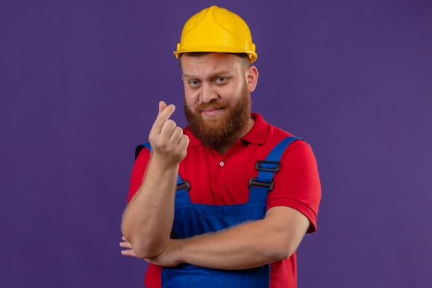 Young bearded builder man in construction uniform and safety helmet displeased making money gesture with hand rubbing fingers asking for money over purple backgroun Free Photo