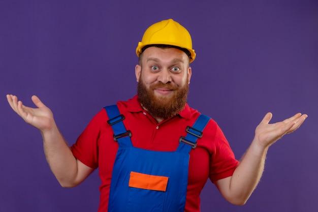 Giovane barbuto uomo costruttore in uniforme da costruzione e casco di sicurezza che sembra sorpreso e confuso sorridente diffondendo palme su sfondo viola Foto Gratuite